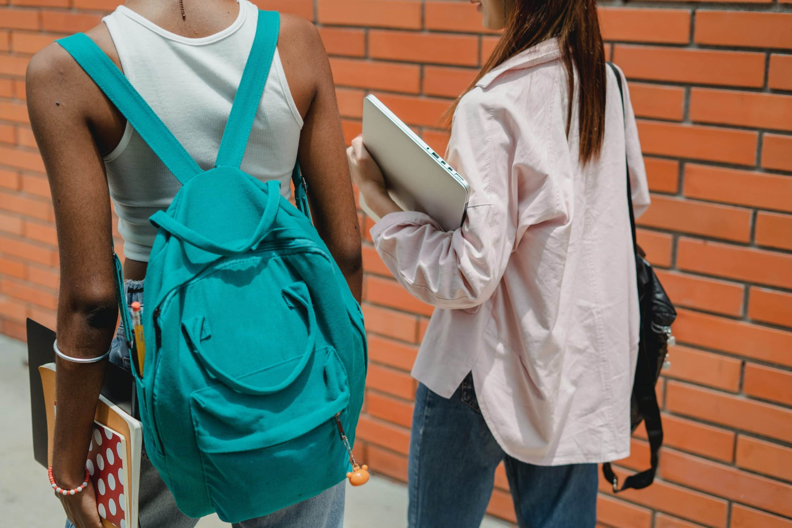 Back view of two teenage students holding books and backpacks